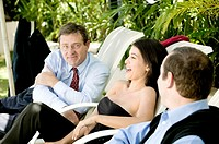 Two businessmen and a businesswoman sitting on lounge chairs