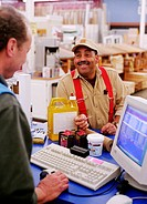 Mature man making purchase at checkout counter in hardware store