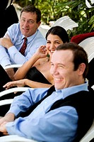 Two businessmen and a businesswoman smiling