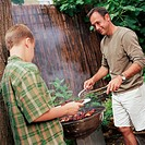 Boy (10-12) watching father grill meat on barbecue