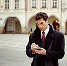 Businessman using palmtop computer outdoors, close-up