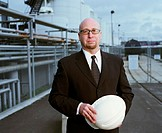 Businessman holding hard hat, standing in front of  industrial plant