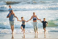 Family walking through surf along beach