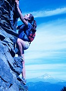 Woman climbing steep rock face, side view, Larch Mountain, Oregon, USA