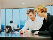Young businesswoman and man at desk in office