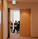 Businessmen meeting in conference room, view through double-doors