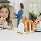 Girl (8-10) eating egg and bread, mom in background, portrait