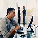 Businessman working on computer, coworkers talking in background
