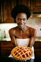 Young woman in kitchen holding cherry pie, portrait