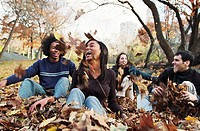 Four young people playing in autumn leaves in park