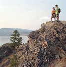 Young couple looking at lake from cliff, low angle view