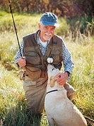 Elderly man with fishing gear, petting Golden Labrador