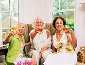 Three mature women toasting with glasses of wine, portrait