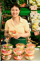 Woman holding carton of fruit salad, smiling, portrait