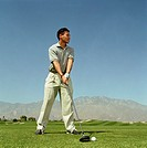 Young man preparing to swing golf club