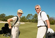 Senior man and woman carrying golf bags on golf course, smiling