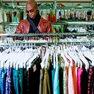 Young man shopping for clothing at thrift store