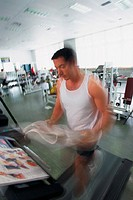 Man on treadmill, reading newspaper