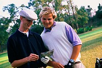 Two men smiling as they go over score card