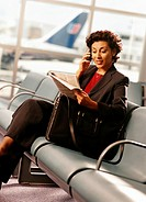 Businesswoman in airport, talking on mobile phone