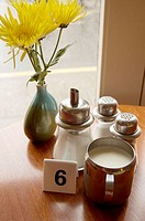 Flowers, sugar, salt, pepper, cream, and a number marker #6 on a table next to a window in a cafe in Portree, Isle of Skye, Scotland, UK