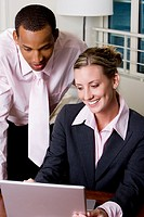 Close-up of a businessman and a businesswoman using a laptop