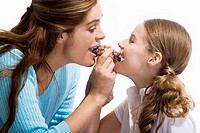 Side profile of a mother and her daughter eating a pastry