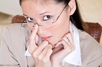 High angle view of a businesswoman with her finger on her eyeglasses
