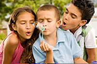 Close-up of a boy blowing bubbles with a girl and a boy beside him