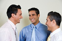Close-up of three businessmen smiling