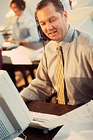 Man talking in headset with printout and computer in front of him
