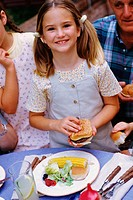 Smiling girl at table holding hamburger