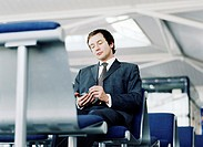 Businessman in waiting lounge of airport using palmtop computer