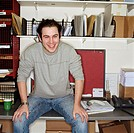 Young man sitting on desk in mail room, smiling