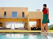 Young woman standing beside swimming pool, holding cell phone