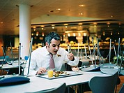 Businessman in canteen eating lunch, chairs stacked on tables