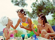 Three young women applying make-up outdoors