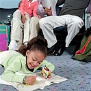 Girl (5-7) coloring on floor of airport waiting area, ground view