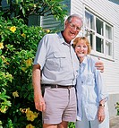 Mature couple outside house, man with arm around woman, portrait
