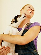 Rat terrier licking woman´s face, woman laughing