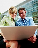 Businessman and businesswoman using laptop outdoors, smiling