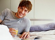 Young man lying on bed by magazine, holding drink, smiling, portrait