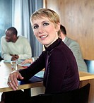 Businesswoman at conference table during meeting, smiling, portrait