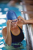 Woman in pool, wearing swimming cap and goggles, smiling