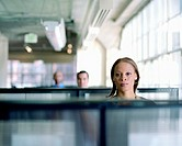 Executives looking over cubicle walls (focus on woman in foreground)