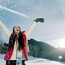 Young woman throwing snow in air, smiling