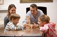 Family playing wooden block game in living room