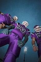 Three high school football players (16-18), night, low angle view