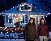 Young couple holding hands in front of home with Christmas lights