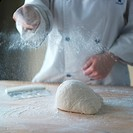 Female baker flouring surface for kneading ball of dough, mid section
